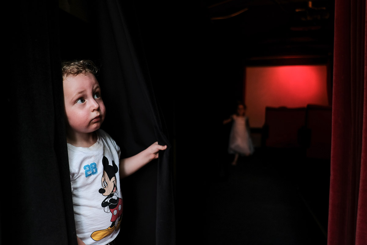 Documentary family photography London. Image by Ben Heasman of a child peering around a curtain.