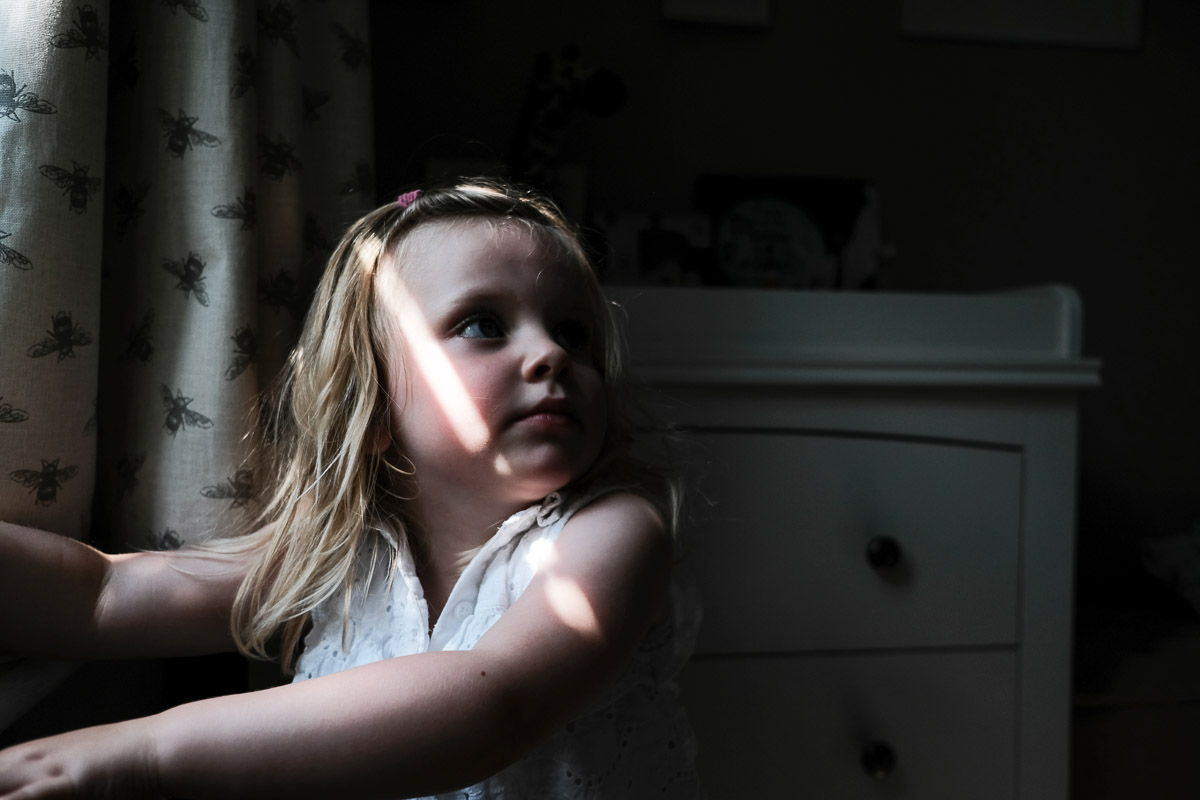 Documentary family photography London. Photograph by Ben Heasman showing child at a window hearing dad calling.
