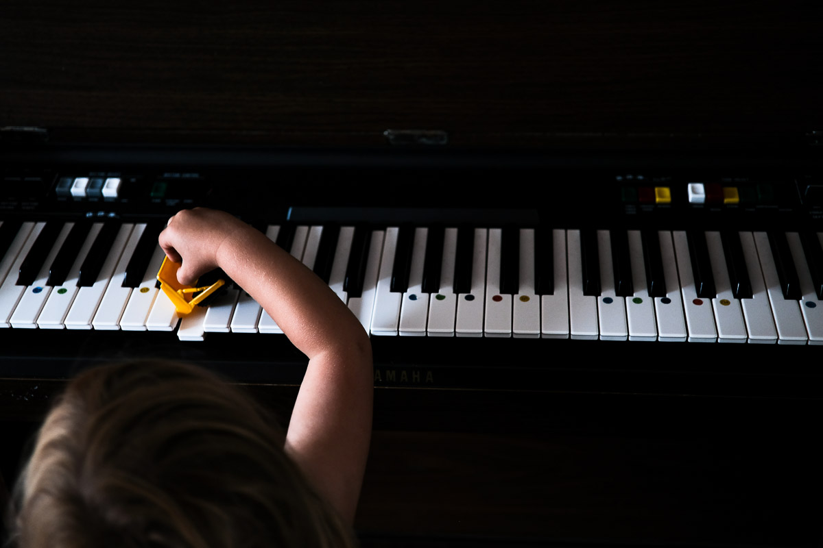 Documentary family photography London. Photograph by Ben Heasman showing a child's unique approach to playing the piano.