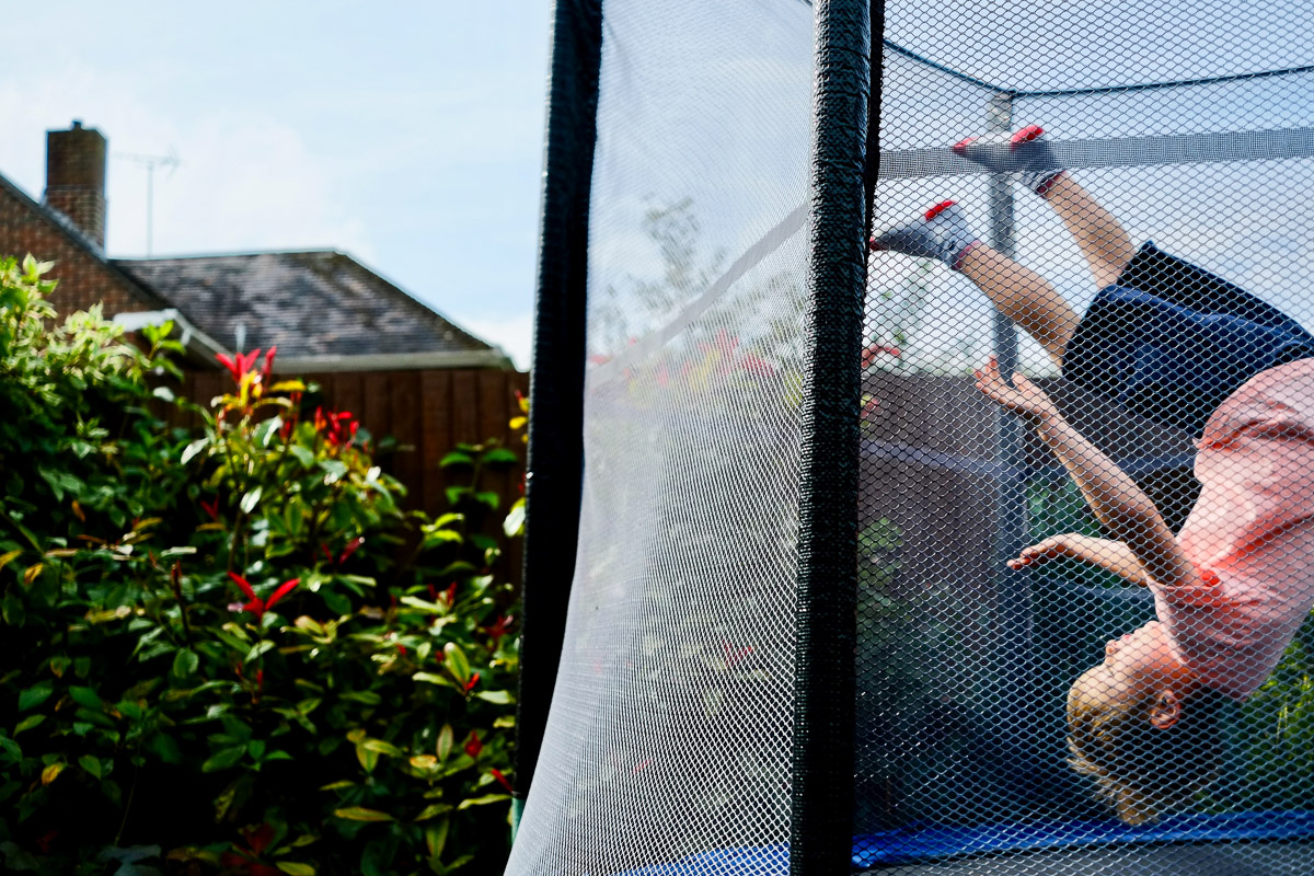 Documentary family photography London. Photograph by Ben Heasman capturing a child having fun flipping on a trampoline.