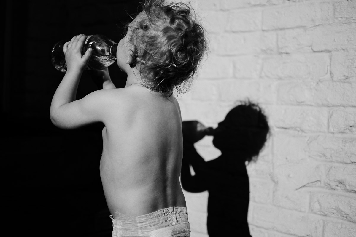Documentary family photography London. Shadow photograph by Ben Heasman of a child drinking in the sun.