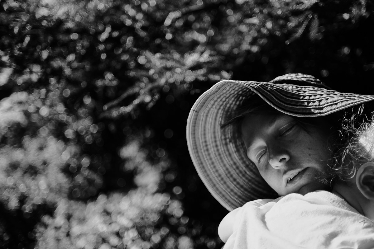 Documentary family photography London. Snapshot by Ben Heasman of a tender embrace between mum and child under the sun.