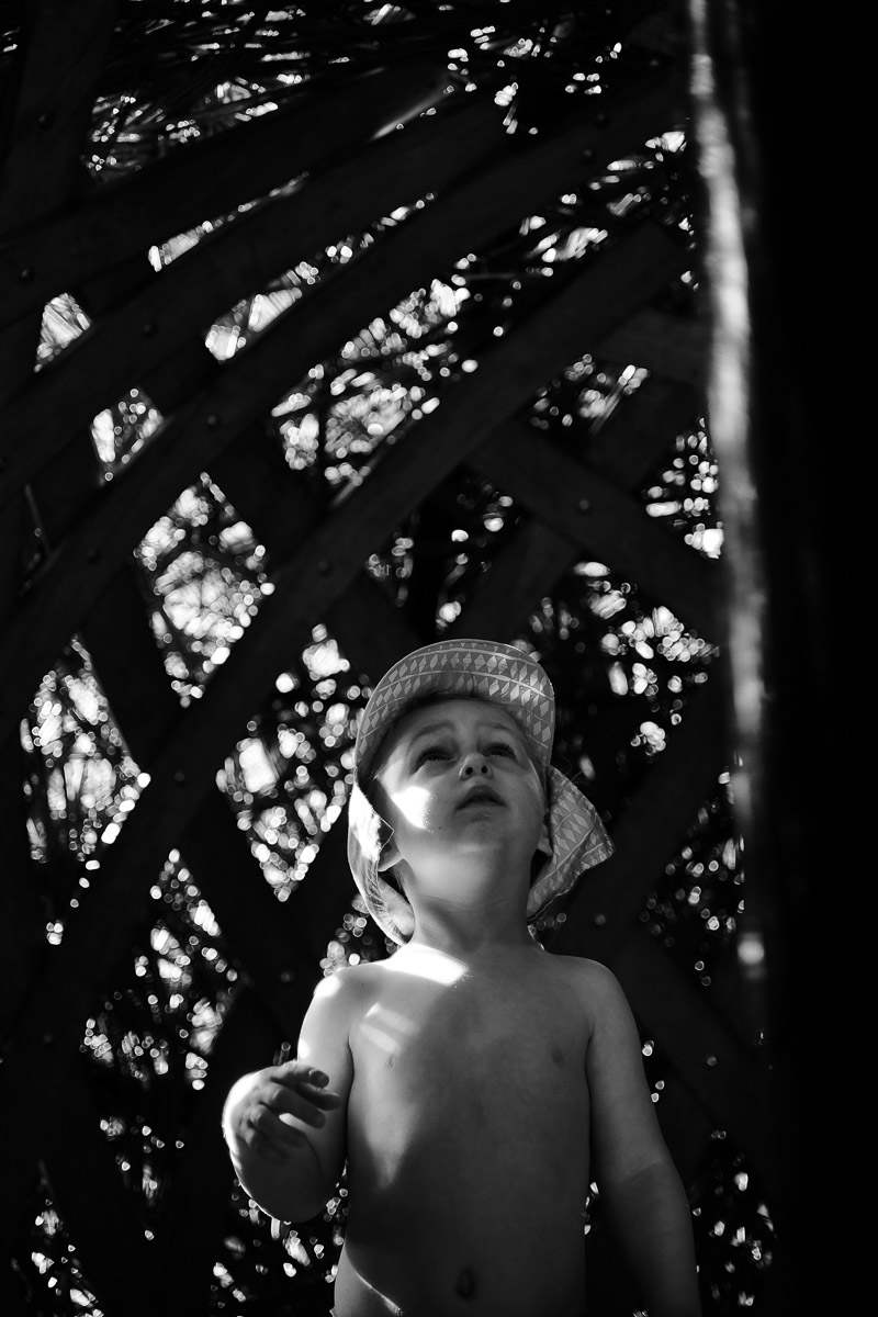 Documentary family photography London. Snapshot by Ben Heasman of a child exploring a treehouse from the inside.