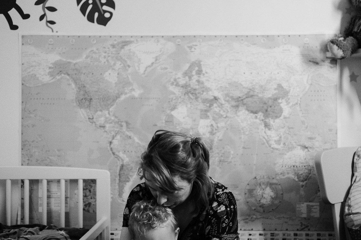 Documentary family photography London. Photograph by Ben Heasman of a mother and child in front of a large map of the world.