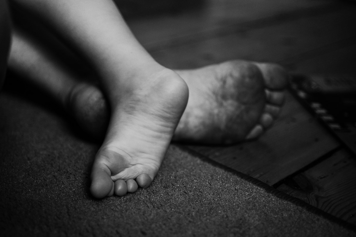 Documentary family photography London. Detail shot by Ben Heasman of mum and child's feet showing their different sizes.