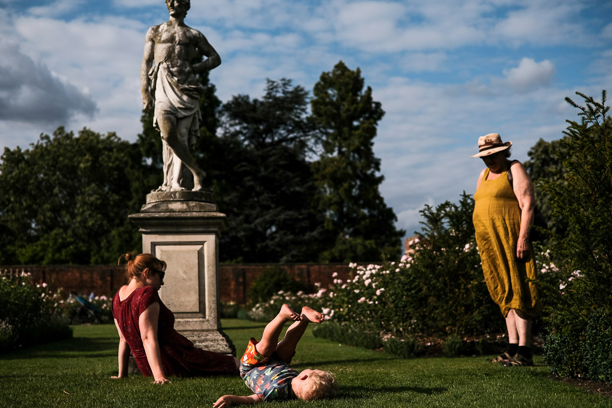 Documentary family photography London. An environmental portrait by Ben Heasman of different family members enjoying the weather, and a nearby statue, outside.