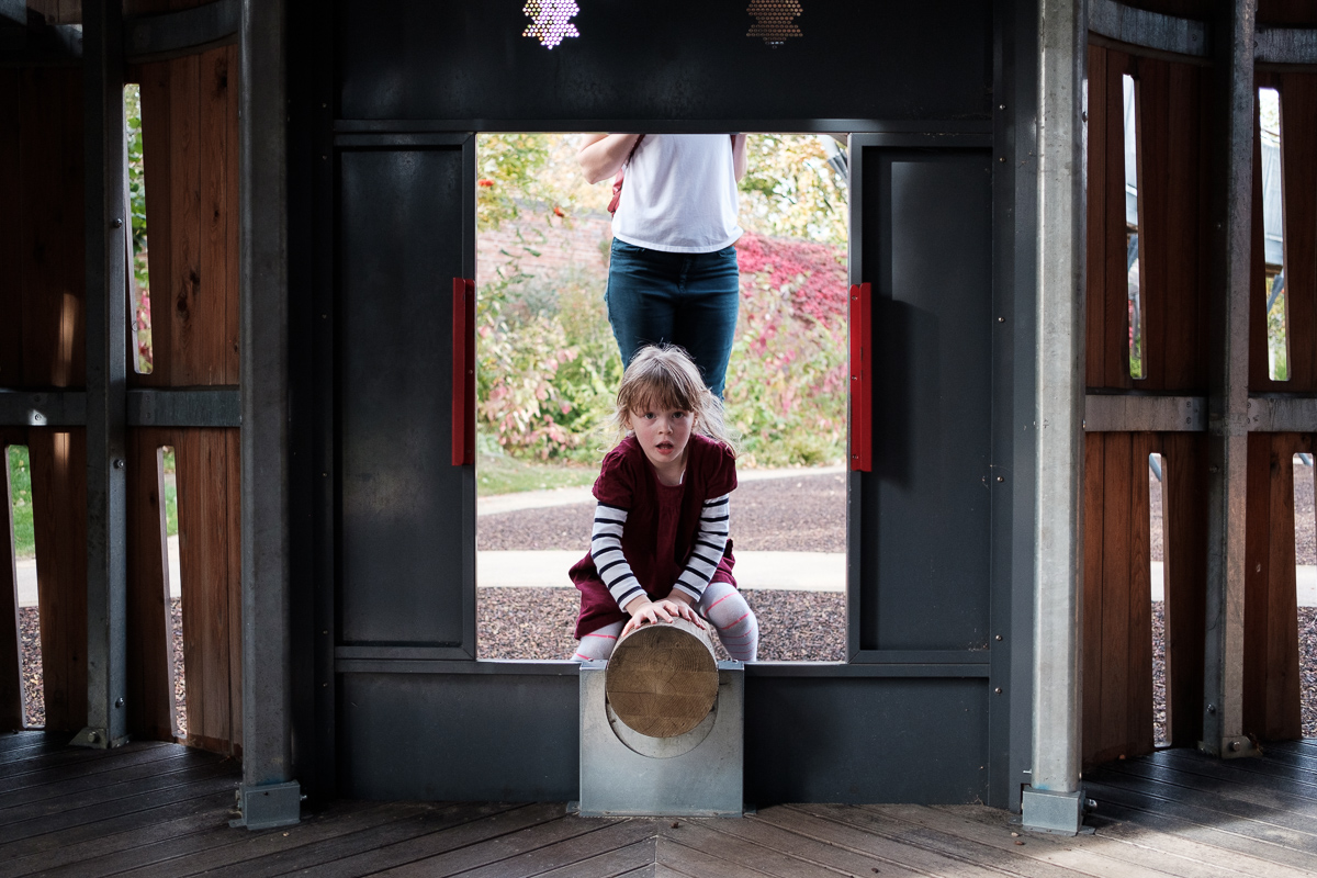Anna navigating a log at a playground.