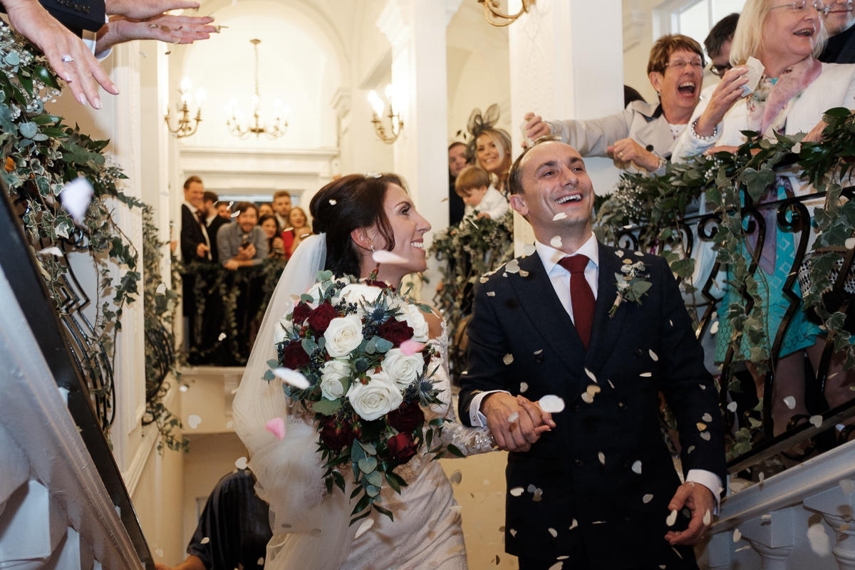 Confetti shower for bride and groom walking up stairs.