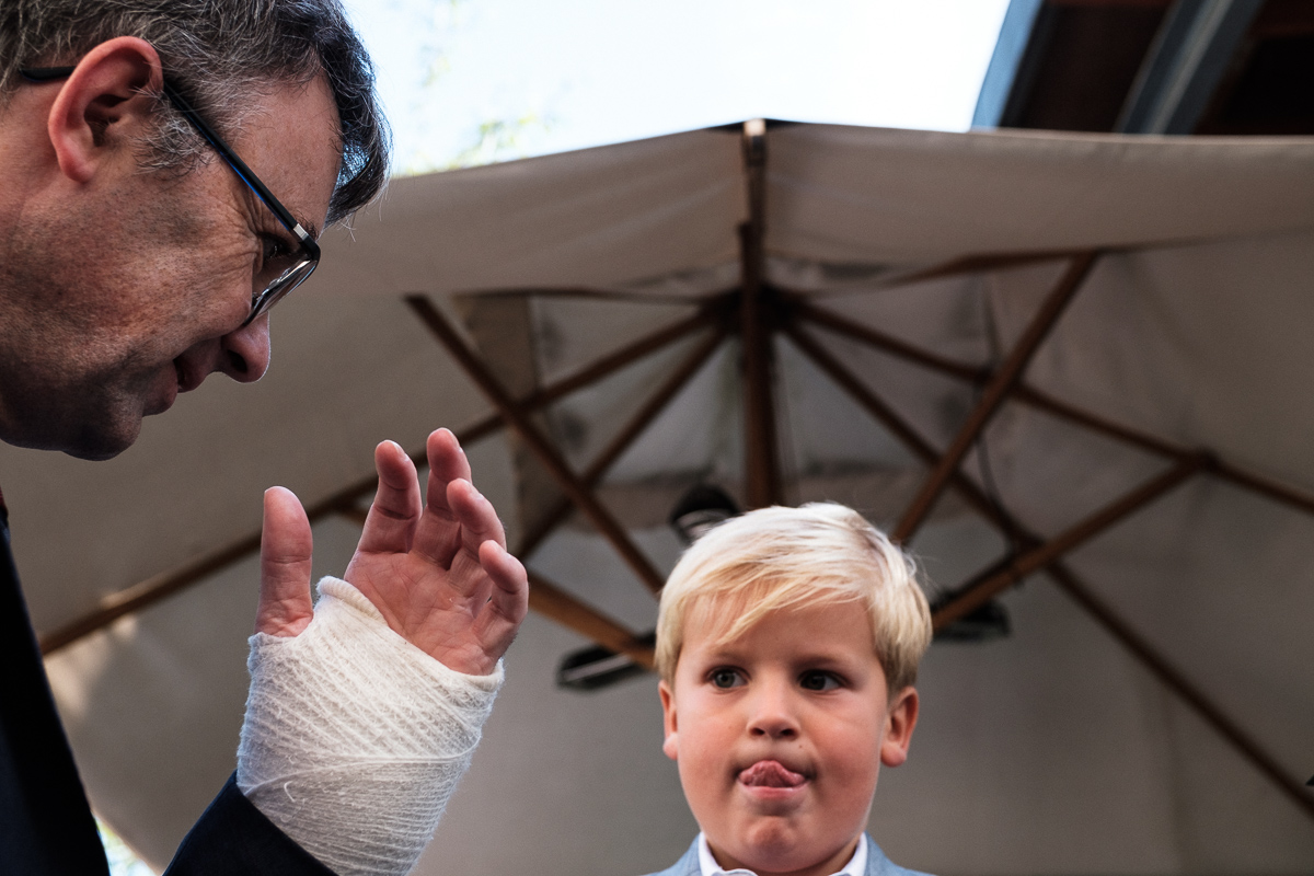 Young child looking at adult's hand with bandage.