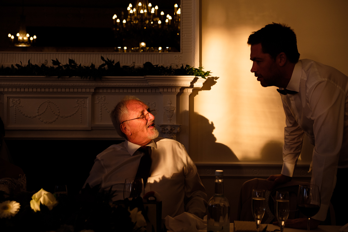 Best man talks with father at wedding reception.