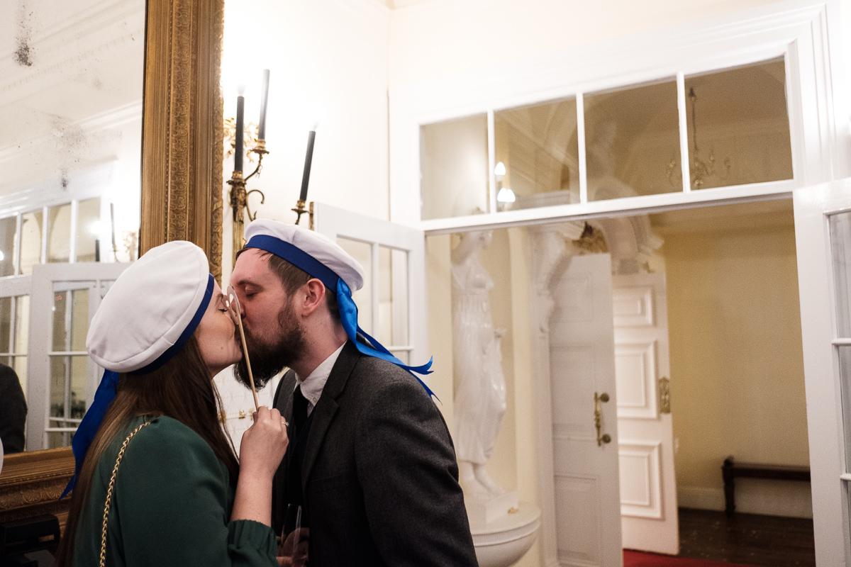 Guests having a kiss at wedding reception.