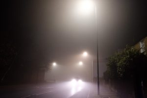 Car on a street in the fog at night