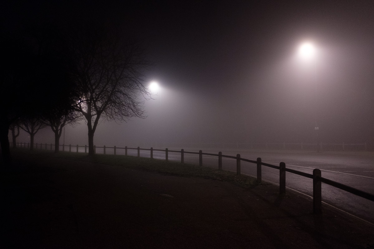The curve of a road in the fog at night.