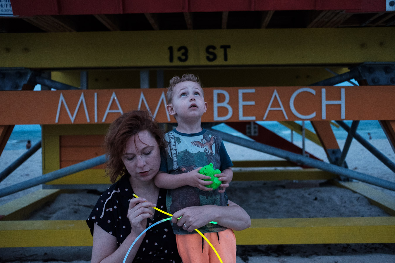 Mum and son playing with glow sticks on Miami beach