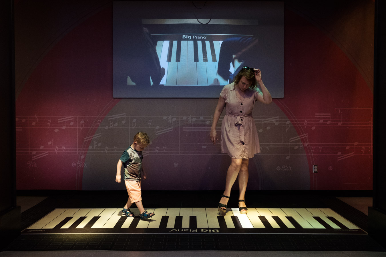 Mother and child playing giant piano keys on the floor