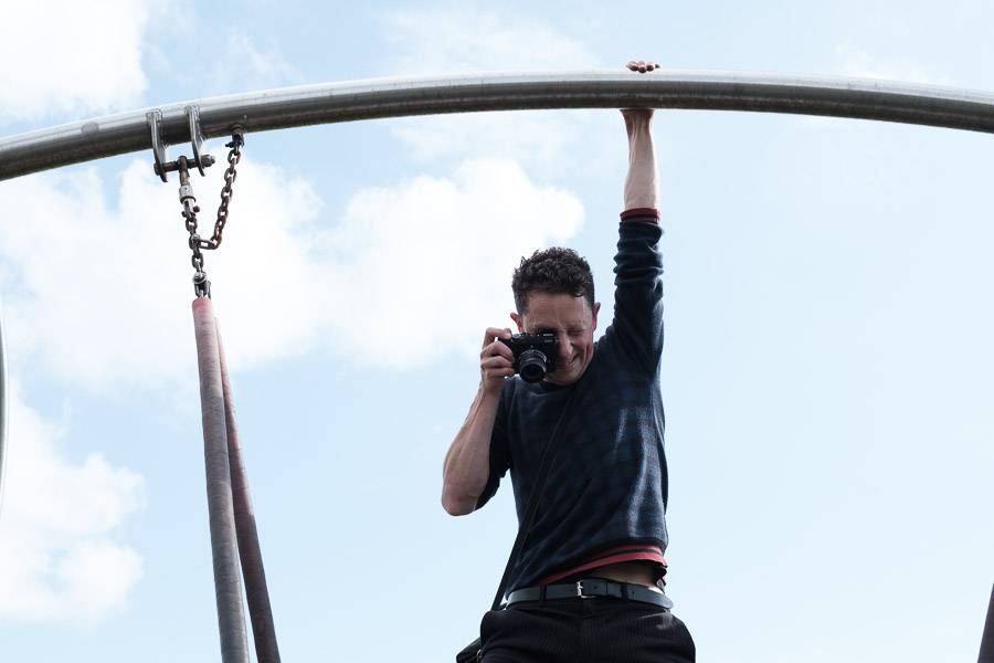 Photographer hanging from a swing taking a photo at a family session.