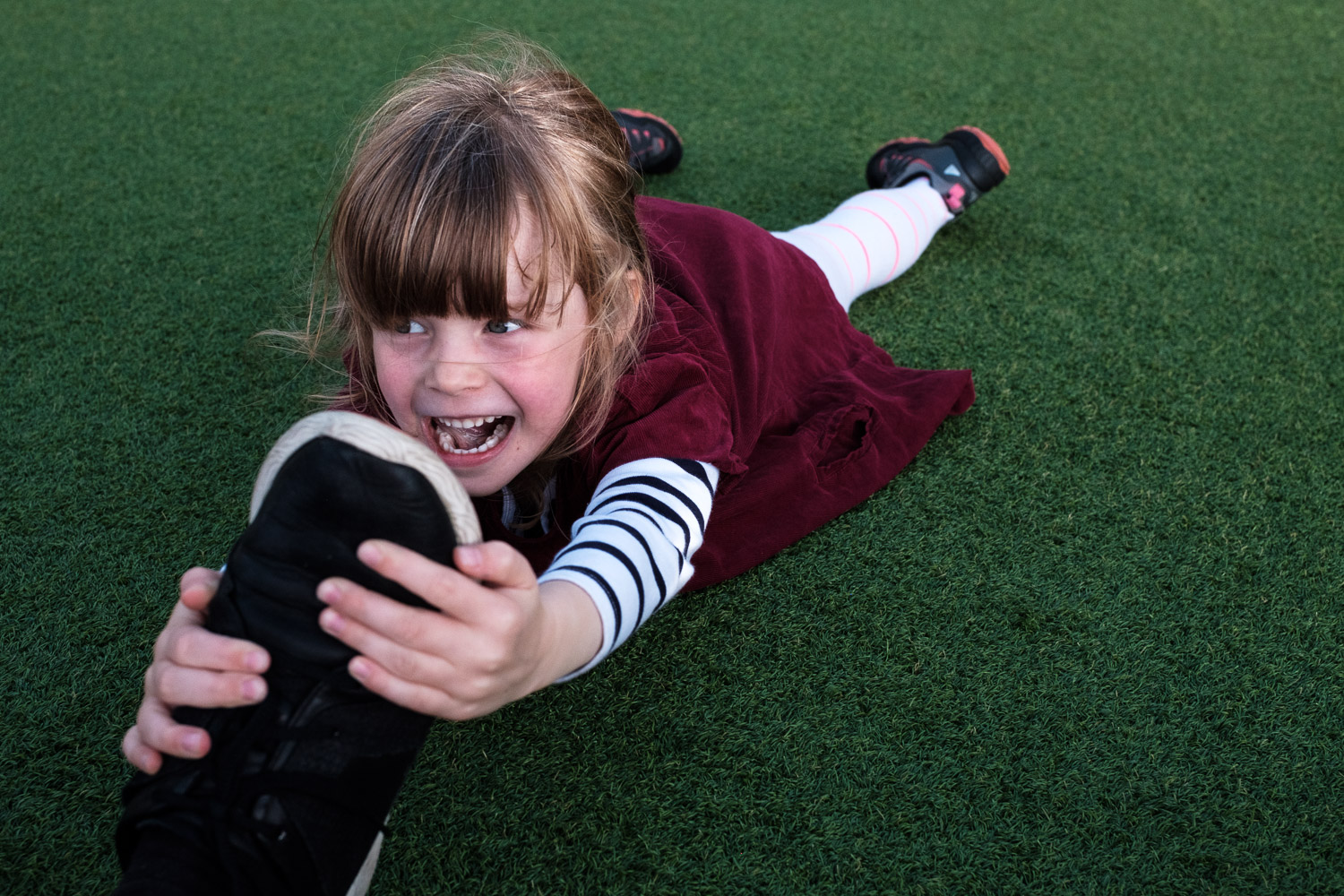 Child gripping onto a shoe and laughing.