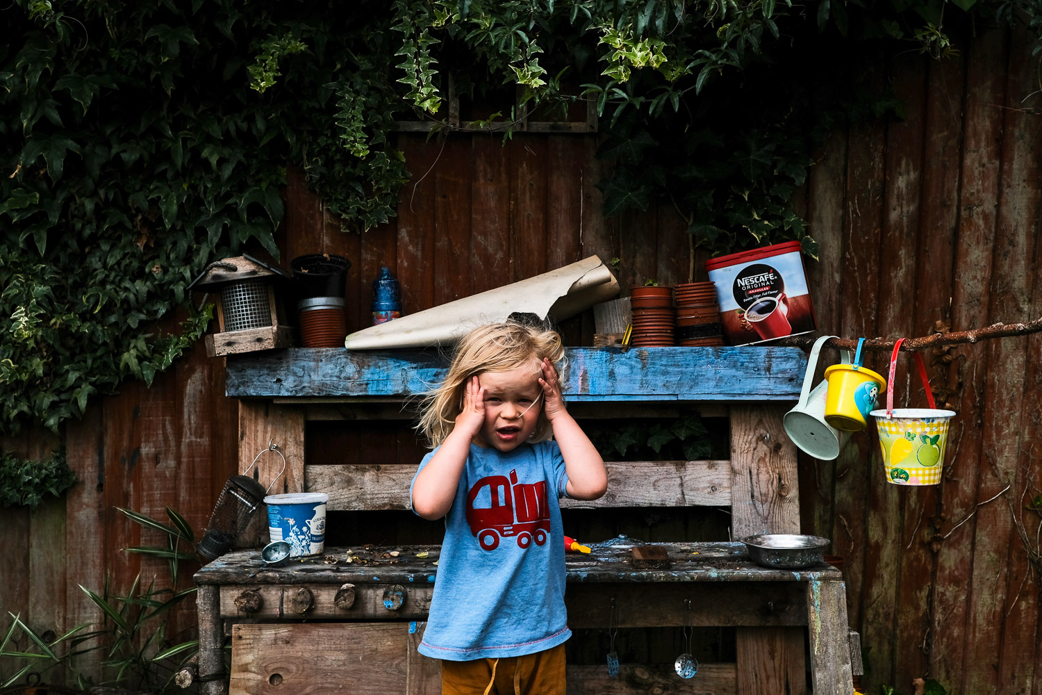 Environmental portrait of child in garden, clasping face with hands.