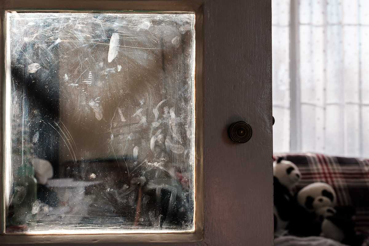 Small child's fingerprints left on a living room window, illustrating an alternative approach to London family photography.
