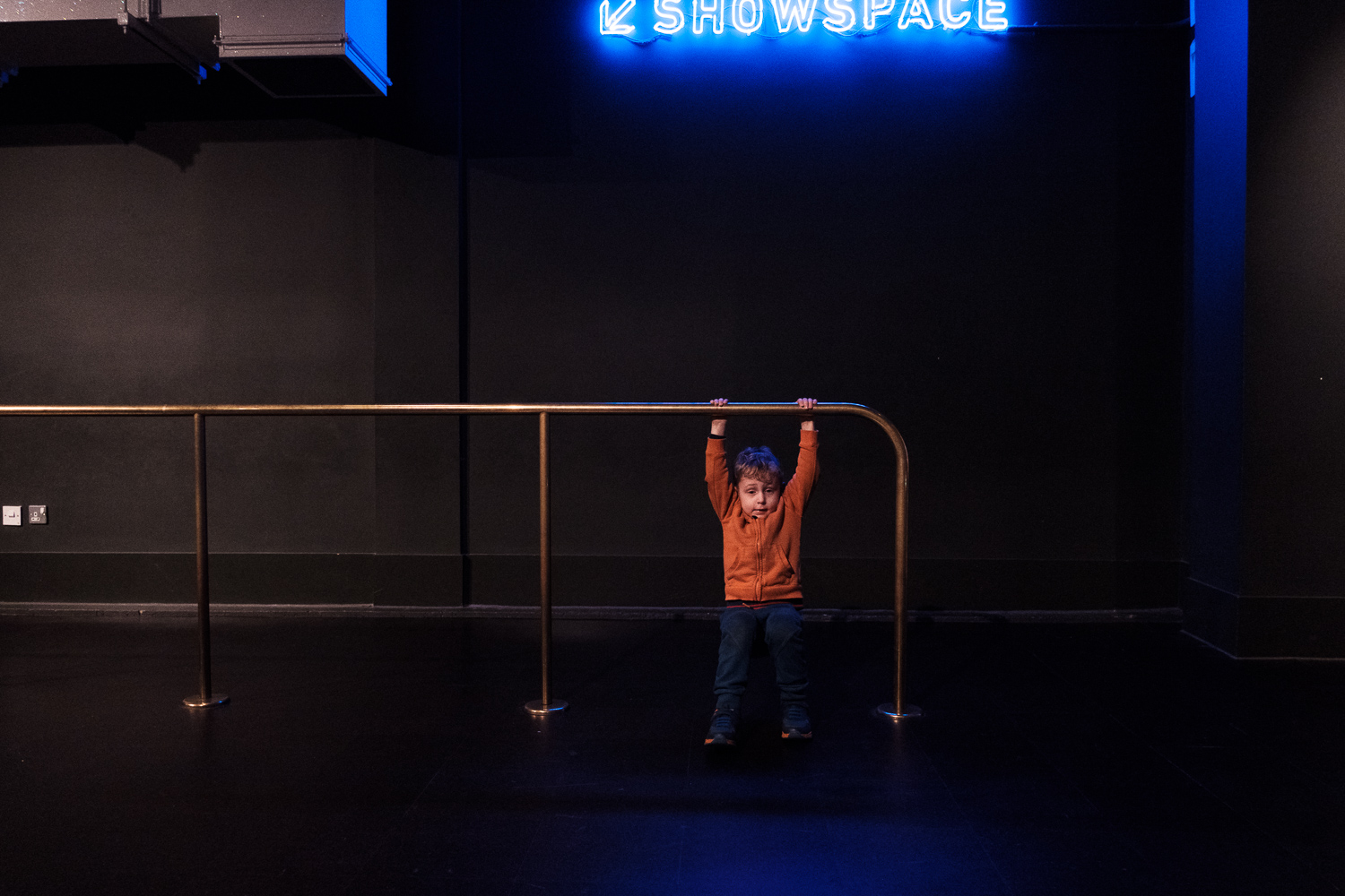Child hanging from a metal railing at a museum.