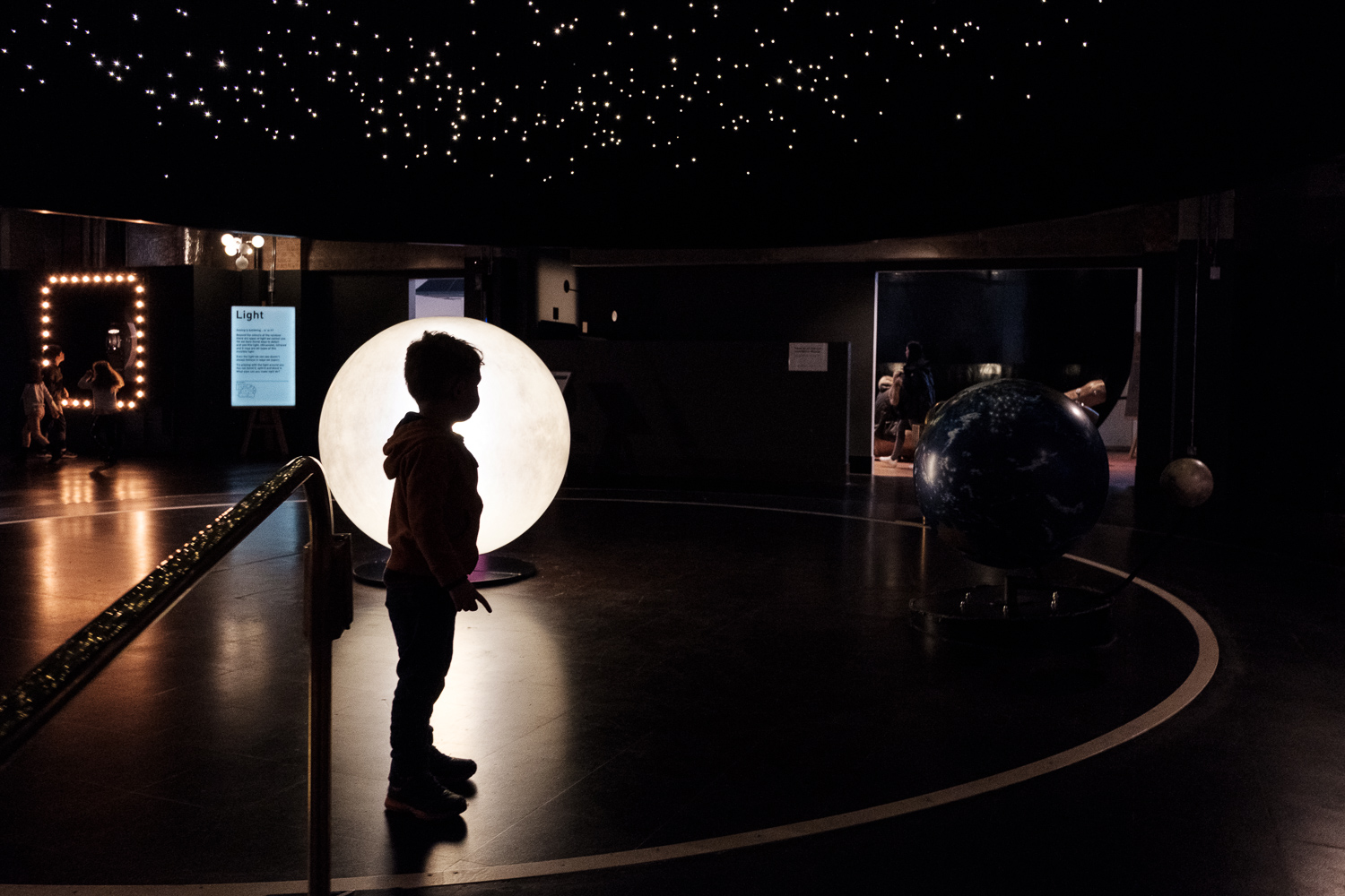Silhouette of a child's figure against a round shape at a museum.