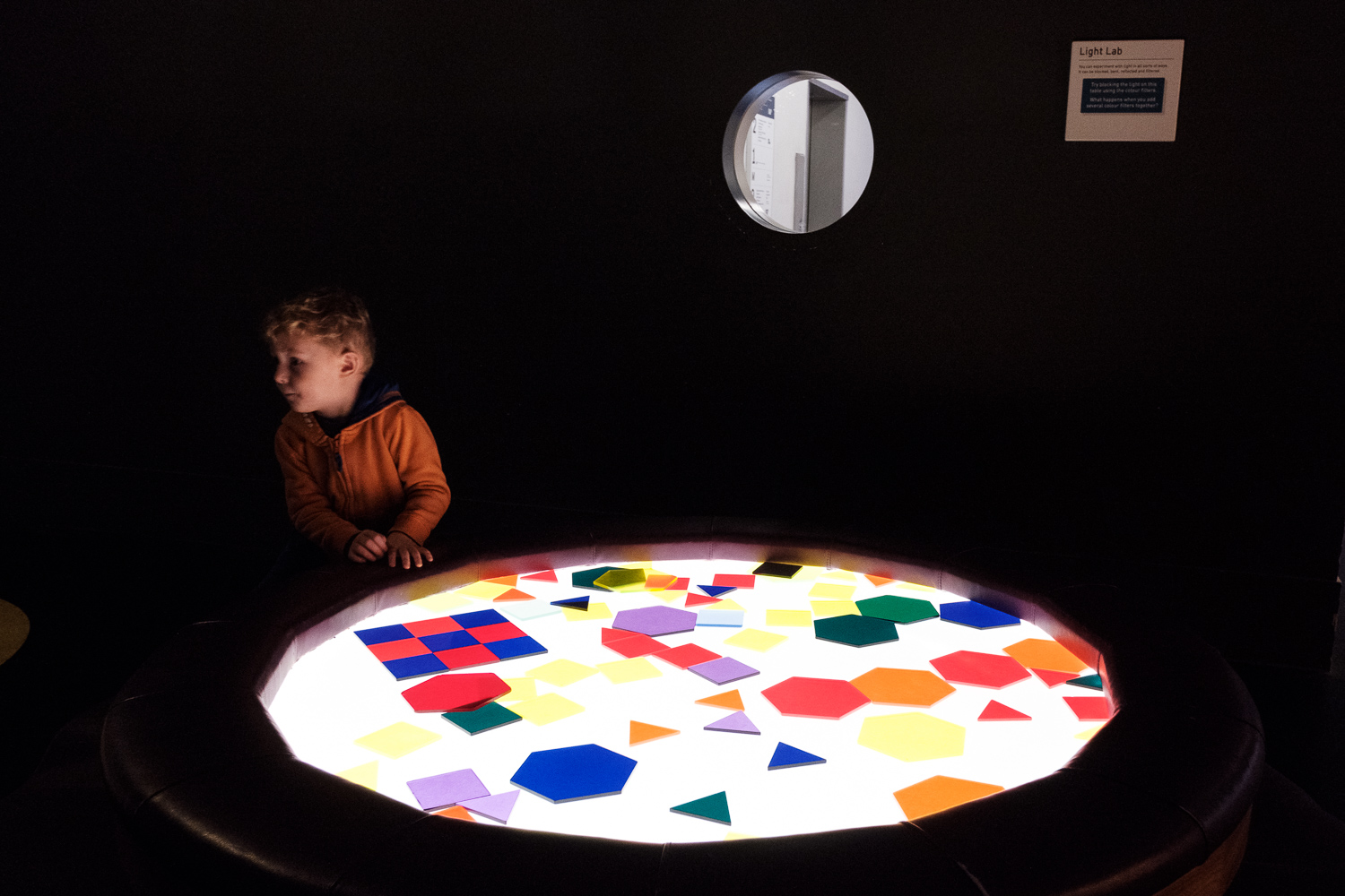 Child exploring an illuminated circular table with coloured shapes.