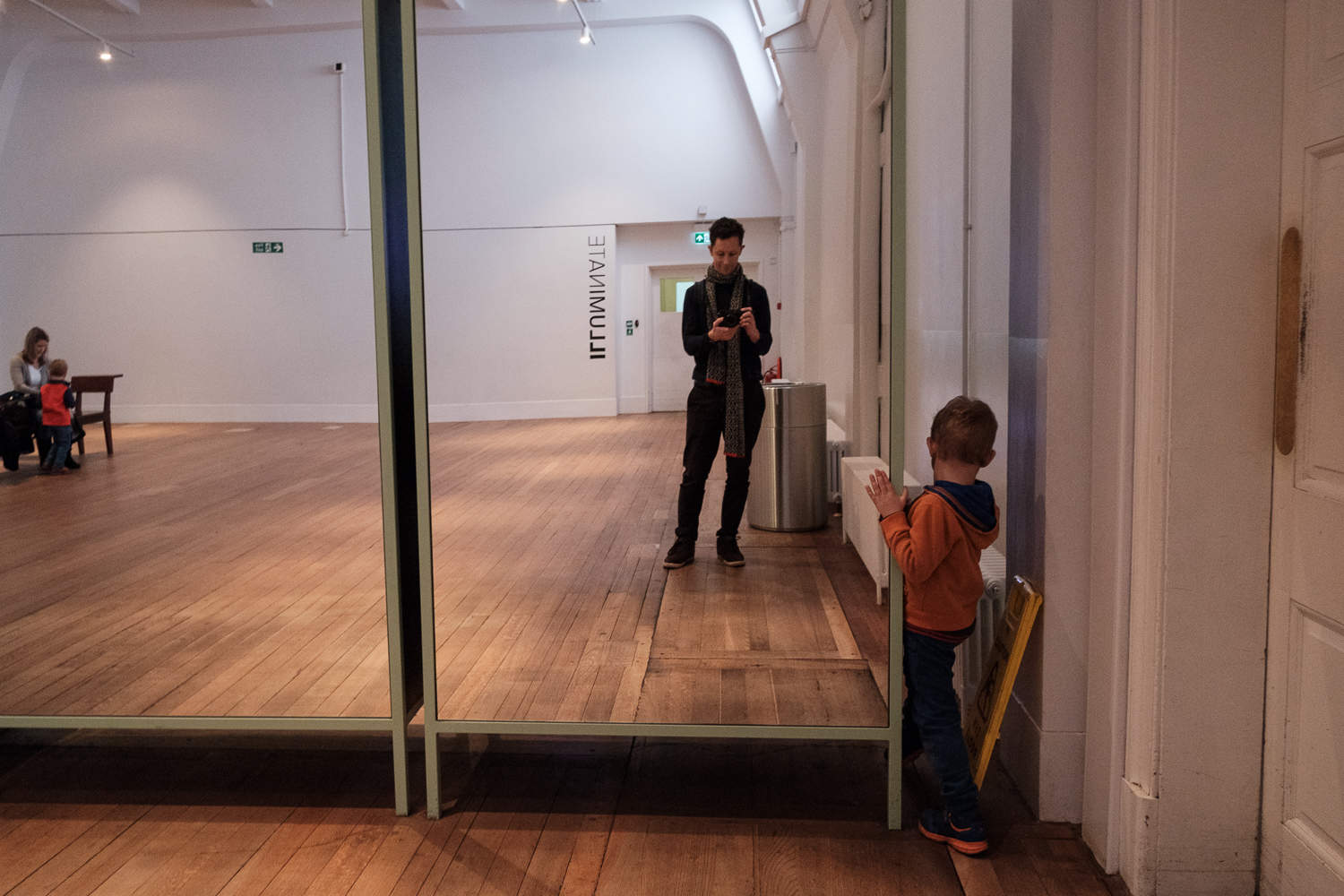 Child exploring behind a mirror at a museum.