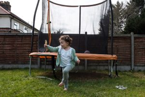 Girl dancing with feather in garden during family photo session.