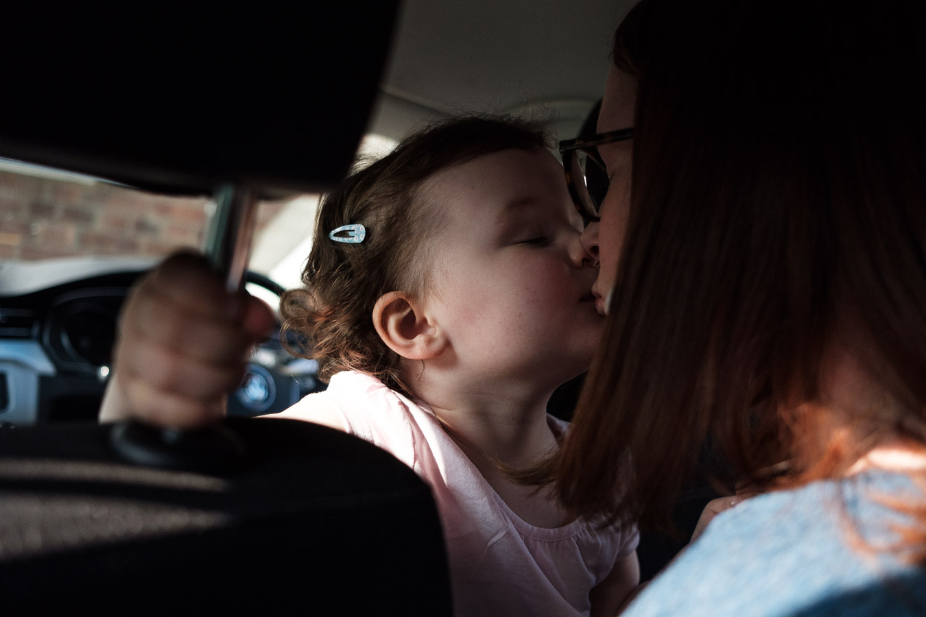 mother and daughter kiss in parked car.
