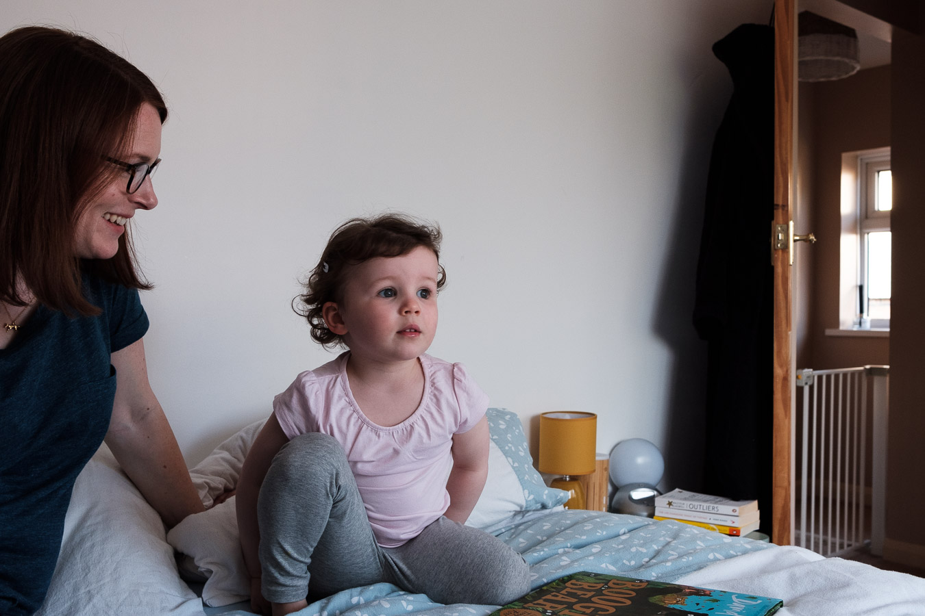Daughter looks up from book her mum is reading to her in bedroom.