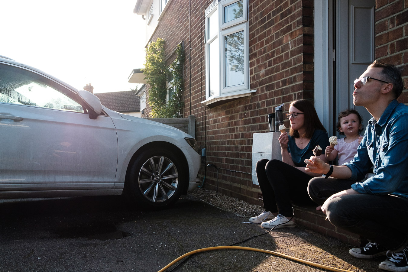 Family relax on front porch with ice creams after a session cleaning car.