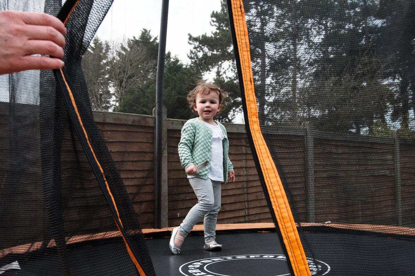 Girl standing on trampoline in garden during family photo session.