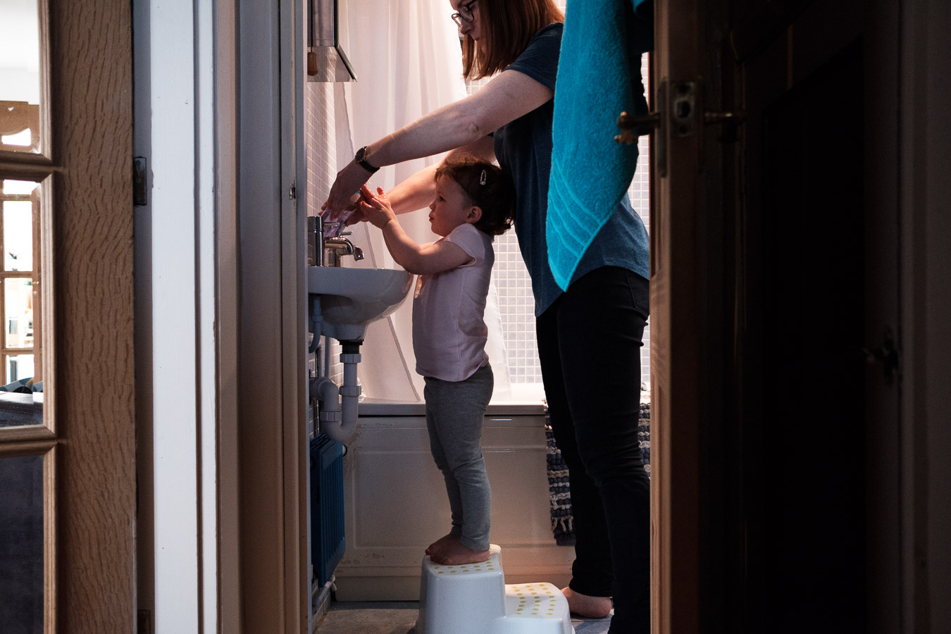 Mum helps daughter wash hands in bathroom during documentary photo session.