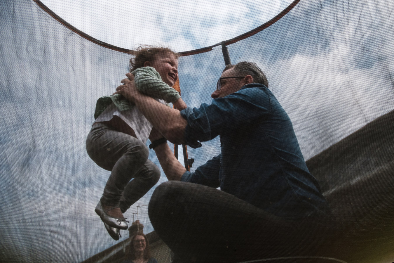 Father and lifting daughter on trampoline whilst mum watches during a family photo session.