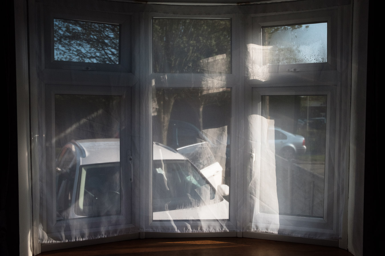 Photo taken from family living room showing recently washed car through a net curtain.
