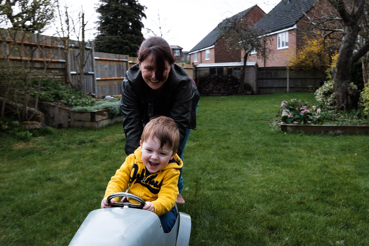 Mum and child outside in a toy car.