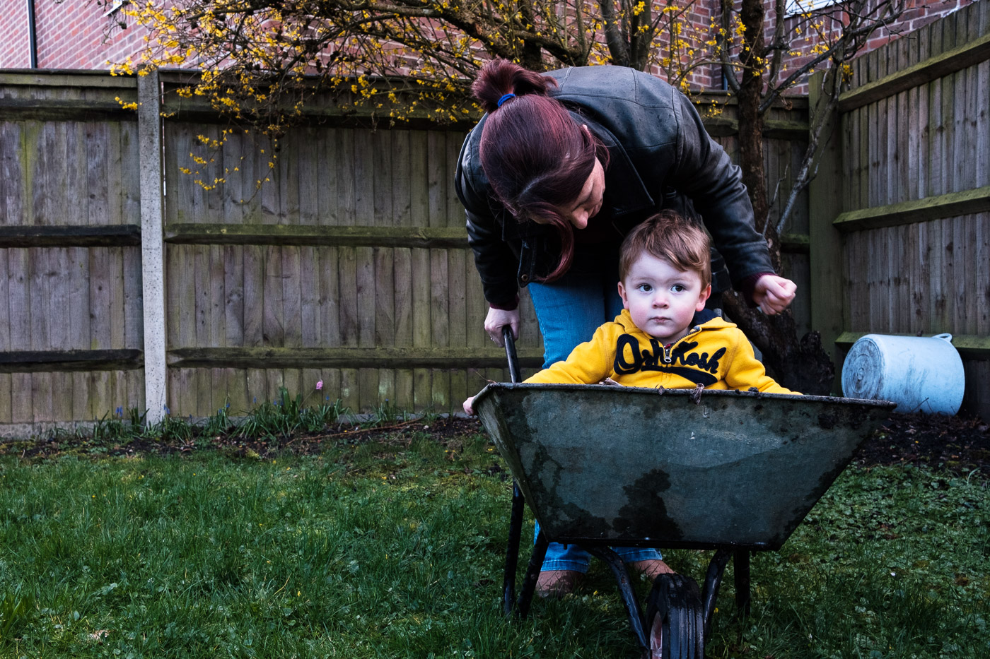 Mum having a word with son who is in a wheelbarrow