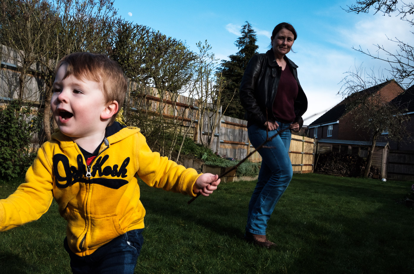Boy running and smiling in the garden with mum watching