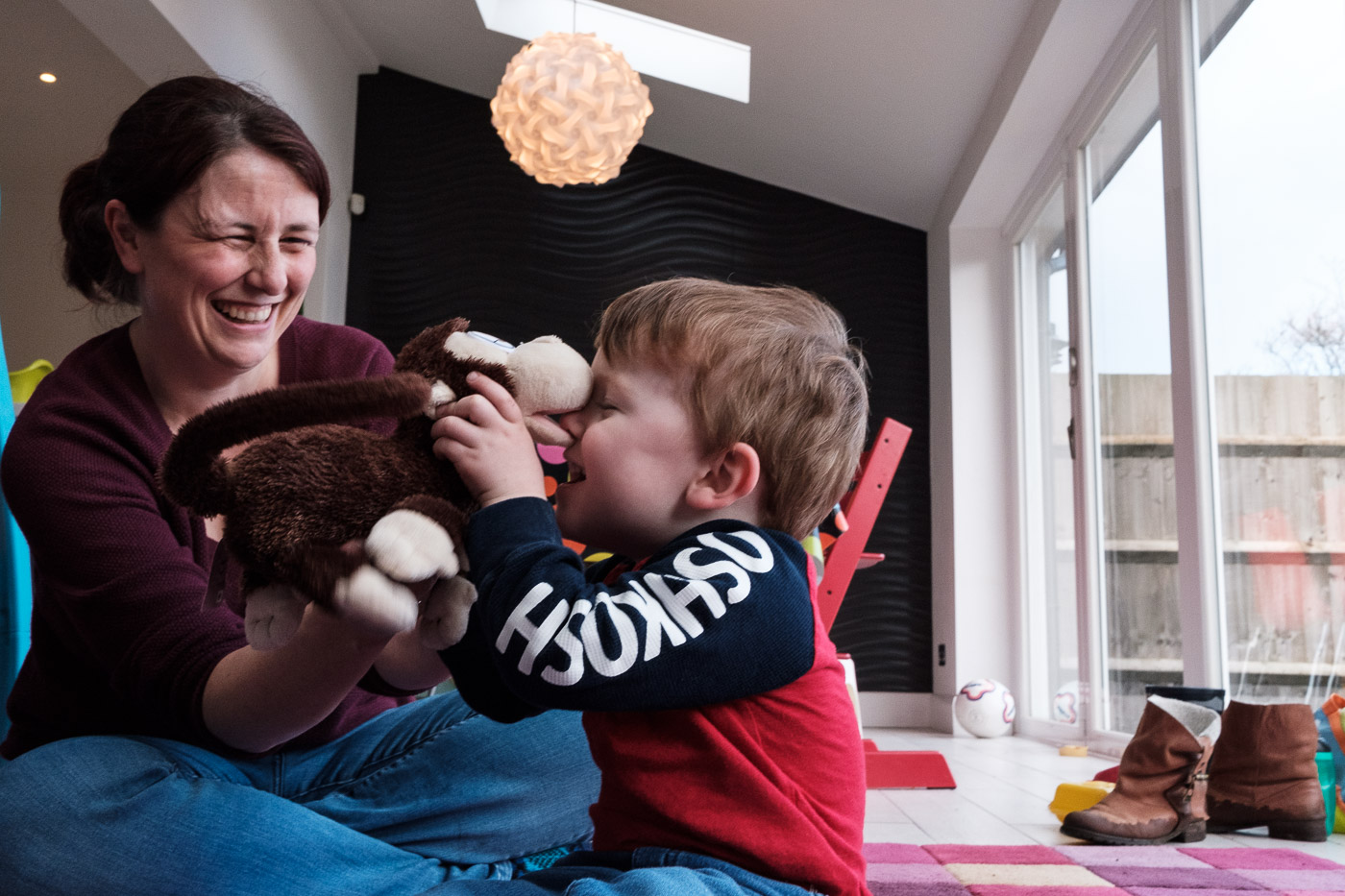 Mother squeezes son's nose with a soft toy