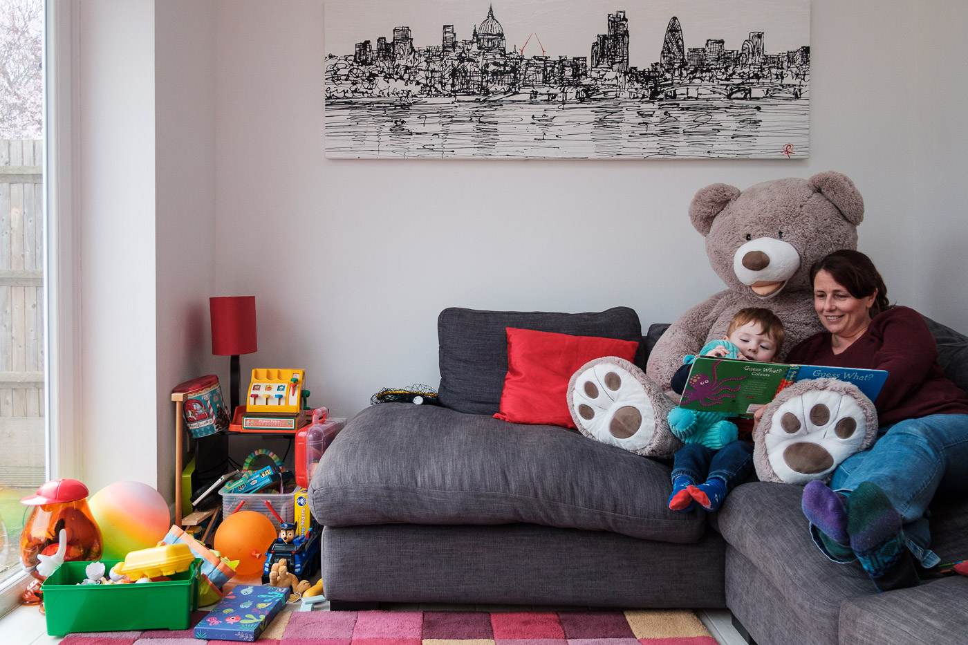 Mother and child reading on sofa with teddy