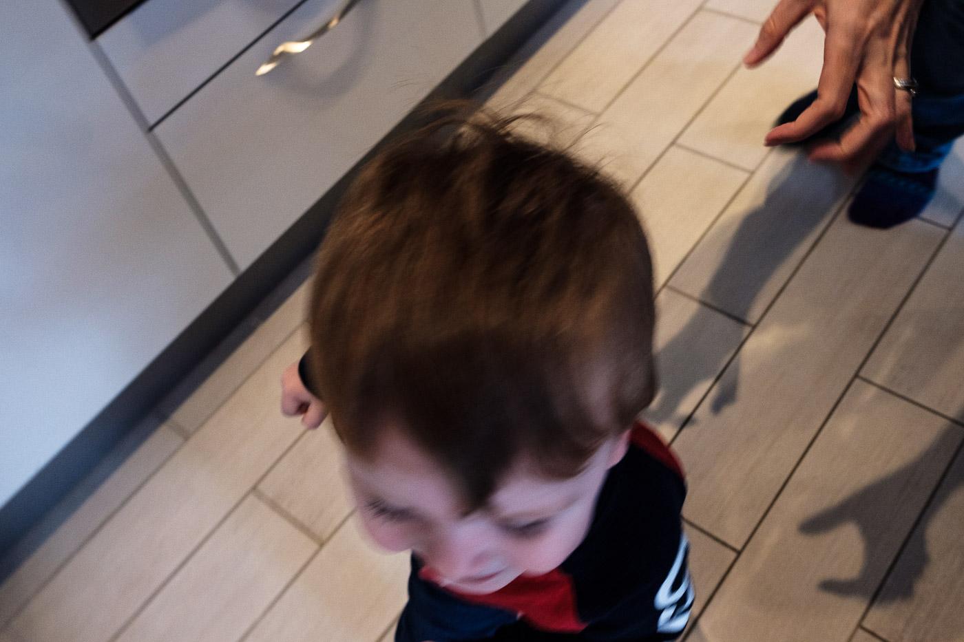 Boy running through the kitchen with hands behind him.