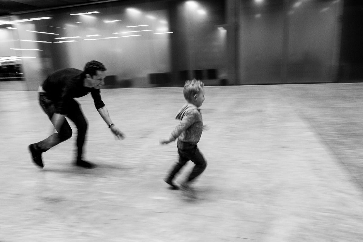 dad and son enjoy a game of chase in a large inside space.