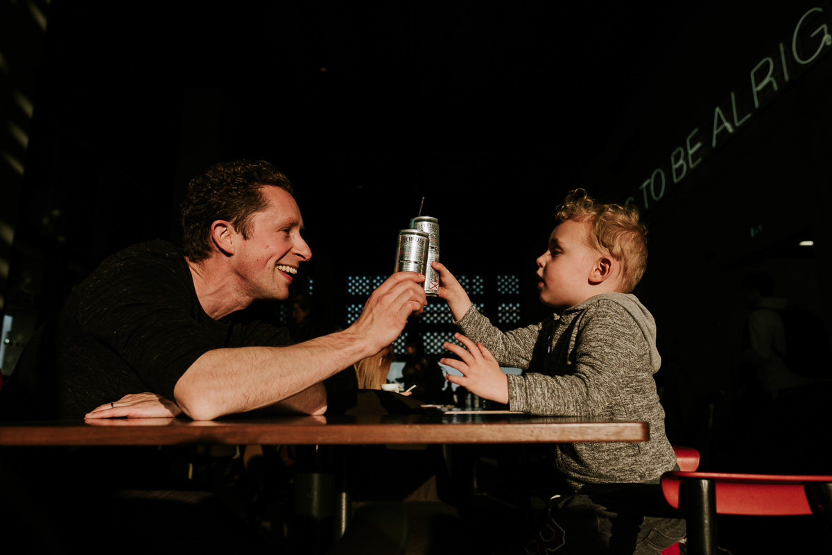 Dad and son enjoy a drink together in a cafe.