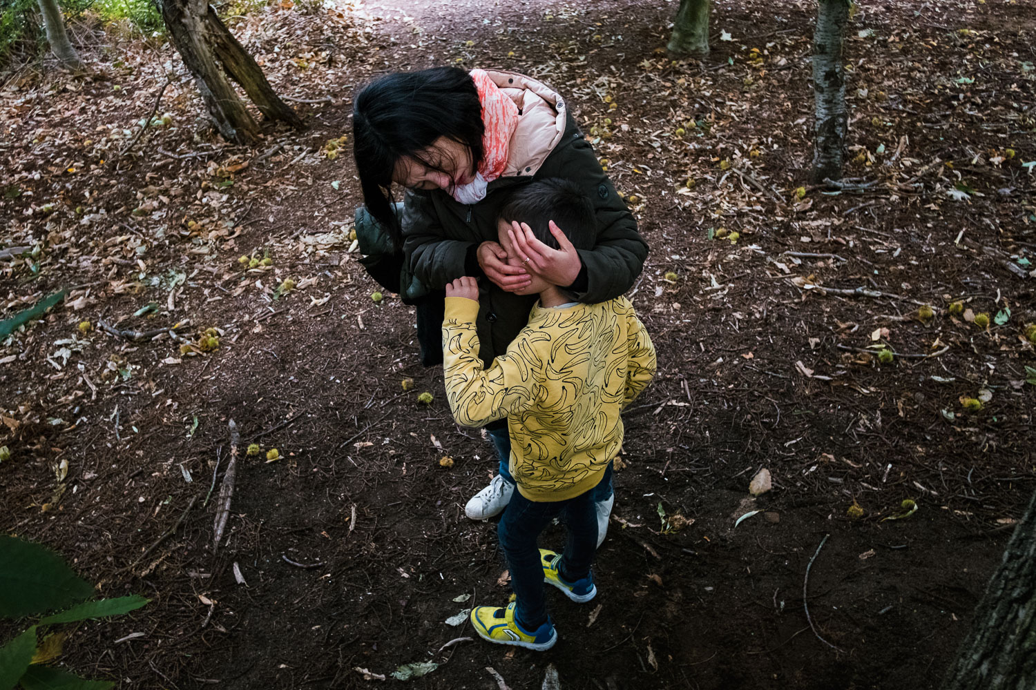 Mother embracing child whilst walking in woods.
