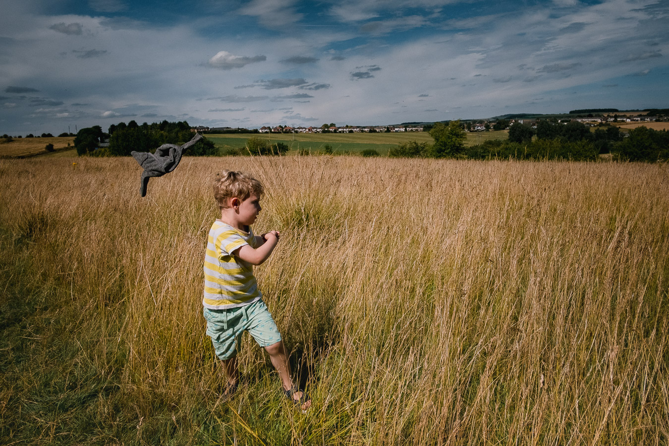Boy throwing jacket in the air in a grassy field
