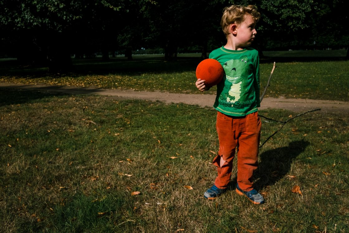 Boy standing with ball and sticks outside